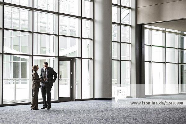 Eine kaukasische Geschäftsfrau und ein Mann bei einem informellen Treffen vor einem großen Fenster in der Lobby eines Kongresszentrums.