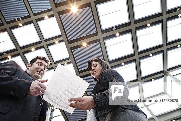 Zwei Geschäftsleute gehen in der Lobby eines großen Kongresszentrums den Papierkram durch.