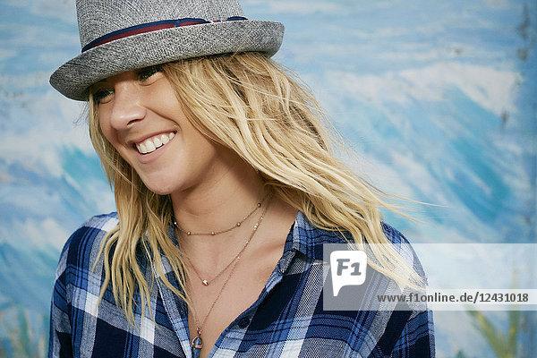Bildnis einer lächelnden Frau mit langen blonden Haaren  blau kariertem Hemd und grauem Trilby-Hut.