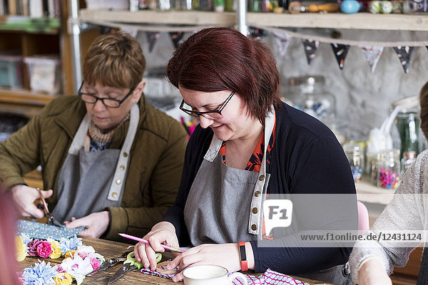Two women sitting at a table in a workshop  making fabric flowers.