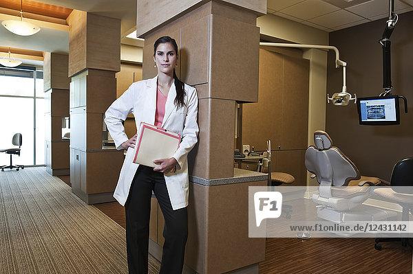 Portrait of an Hispanic dentist in her dental office.