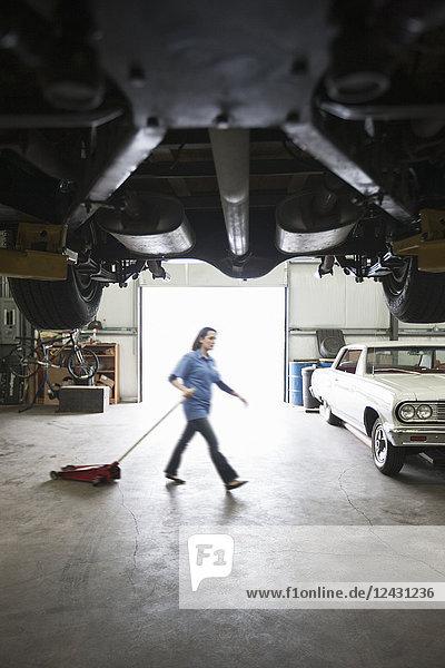 Eine Automechanikerin zieht einen tragbaren Wagenheber über den Boden der Autowerkstatt.