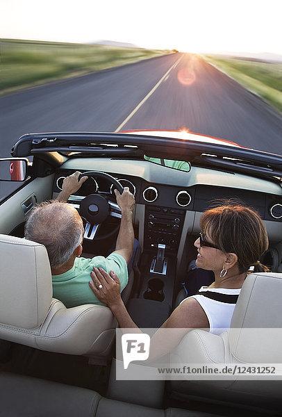 Ein Blick von hinten auf ein älteres Ehepaar in einem Cabrio-Sportwagen  das bei Sonnenuntergang im Osten des Bundesstaates Washington  USA  auf einer Autobahn fährt.