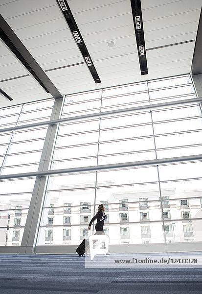 Geschäftsfrau  die durch die Lobby eines Konferenzzentrums läuft.