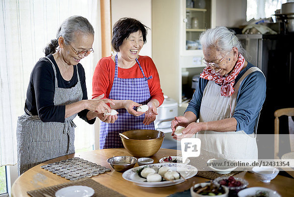 Three older women standing round a table in a kitchen  making sushi.