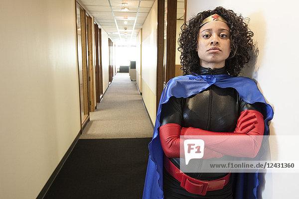 Der Superheld einer schwarzen Geschäftsfrau steht in einem Flur ihres Büros.