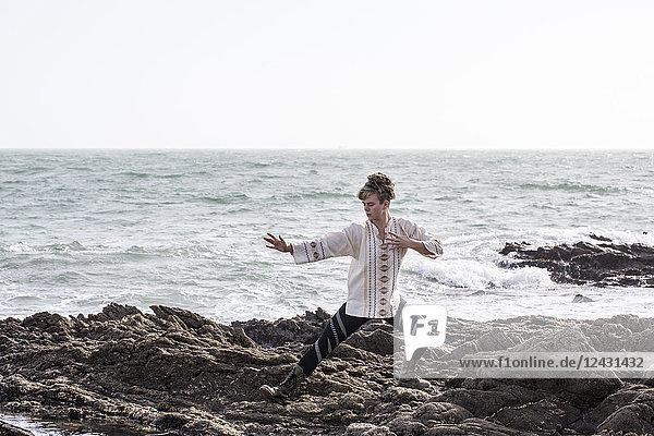 Junge Frau mit braunen Haaren und Dreadlocks in weißer Bluse  die am felsigen Ufer am Meer steht und Tai Chi macht.