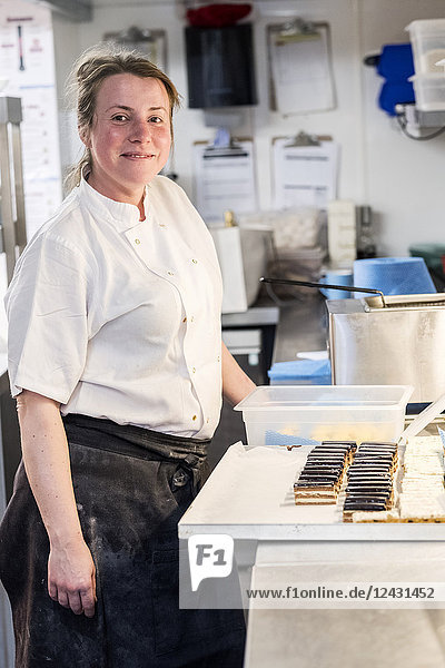 Female chef wearing chef's whites and apron standing at counter with tray of cakes in commercial kitchen.