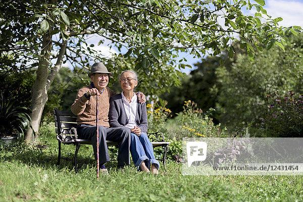 Ehemann und Ehefrau  älterer Mann mit Hut und Frau sitzen nebeneinander auf einer Bank in einem Garten.