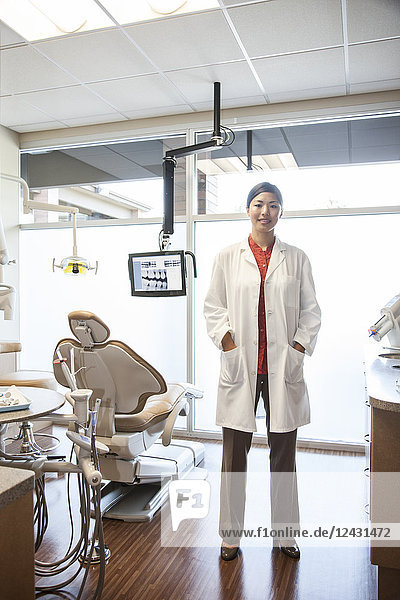 A portrait of an Asian female dentist in her office.