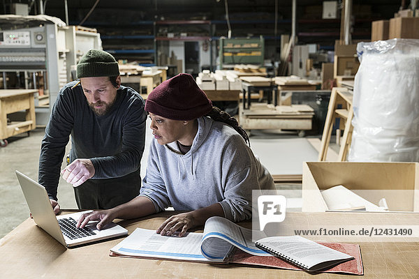A Caucasian male carpenter and a Black female carpenter working on a laptop computer after work hours in a large woodworking factory.