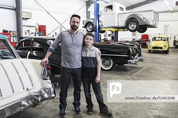 A portrait of a Caucasian male and his young son in their classic car repair shop.