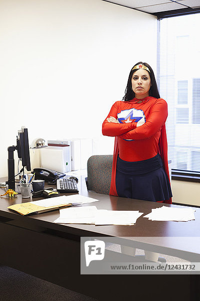 An Hispanic businesswoman office super hero at her office computer