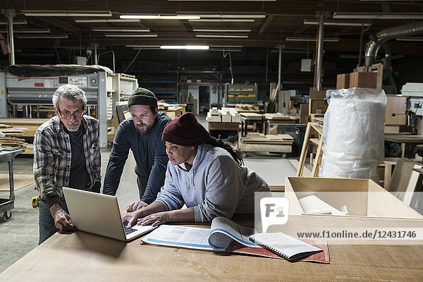 Three mixed race carpenters working on a laptop computer after work hours in a large woodworking factory.