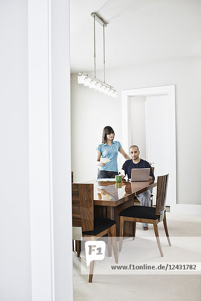 Hispanic man and woman looking at a lap top computer on the dinning room table of a new home.