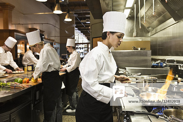 A crew of chef's working in a commercial kitchen  with a black chef in the foreground sauteing vegetables.