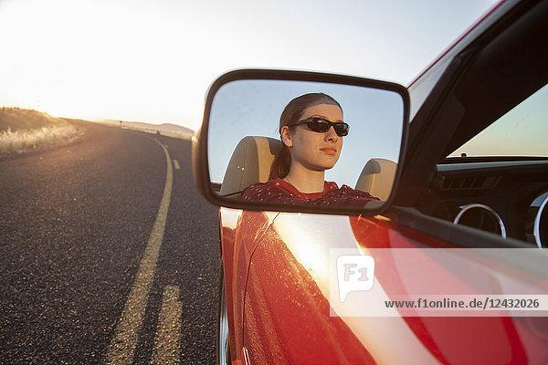 Eine junge Kaukasierin spiegelt sich im Seitenspiegel eines Cabrio-Sportwagens auf der Autobahn.