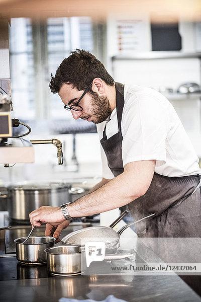 Bärtiger Koch mit Brille und Schürze  der in der Großküche am Herd steht und Speisen im Topf umrührt.