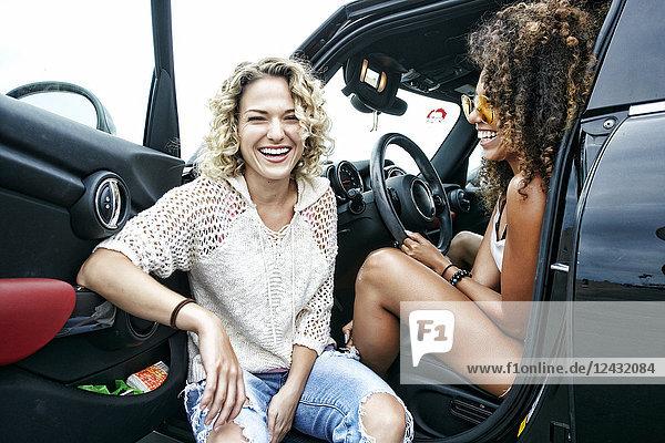 Porträt von zwei lächelnden jungen Frauen mit blonden und braunen Locken  die im geparkten Auto sitzen und in die Kamera schauen.