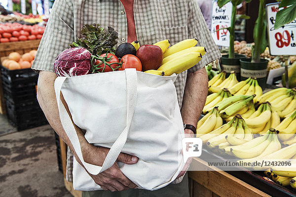 Close up of person at a food and vegetable market  holding shopping bag with fresh produce including bananas  tomatoes and cabbage.