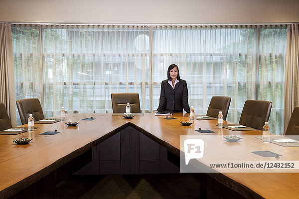 Asian businesswoman at the head of a conference room table.
