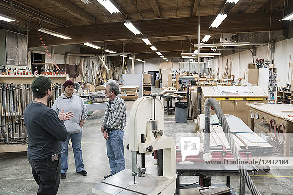 Eine Gruppe gemischtrassiger Tischler  die an einem Arbeitsplatz in einer großen Holzwerkstatt ein Projekt diskutiert.