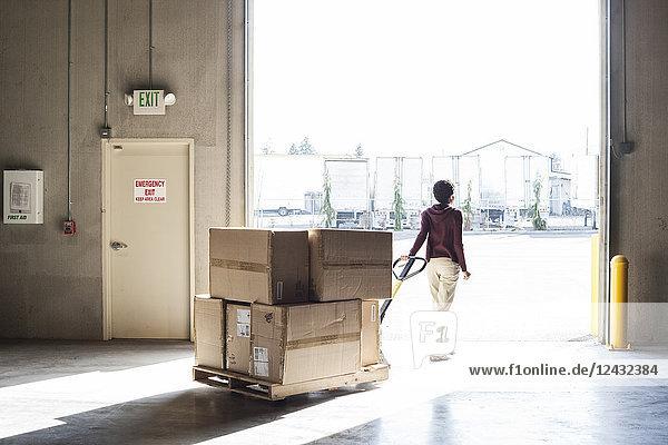 Eine Lagerarbeiterin  die in einem Vertriebslager Produkte in Kartons mit Hilfe eines manuellen Palettenwagens bewegt.