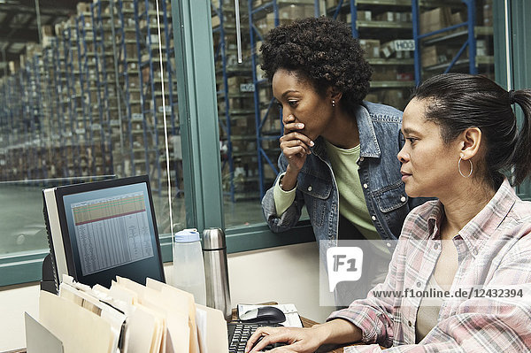 Team of two African American female warehouse workers working on a computer in an office in the middle of a large distribution warehouse full of racks of products stored in cardboard boxes on pallets.