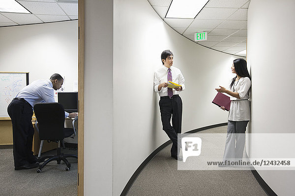 Two Asian businesspeople talking in a hallway near a black businessman working alone in his office.
