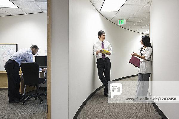 Zwei asiatische Geschäftsleute unterhalten sich in einem Flur in der Nähe eines schwarzen Geschäftsmannes  der allein in seinem Büro arbeitet.