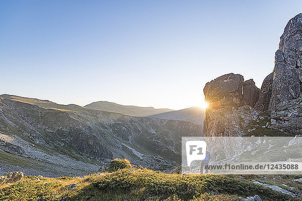 The last rays of sun disappear behind a rock face after a day of trekking in the Rila Mountains  Bulgaria  Europe