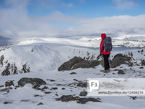 A winter walker on the summit of The Cairnwell in the Cairngorm National Park looking over to Carn a' Gheoidh  Cairngorm National Park  Scotland  United Kingdom  Europe