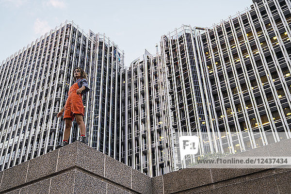 Beautiful woman wearing dungarees  standing on ledge in front of modern high-rise building