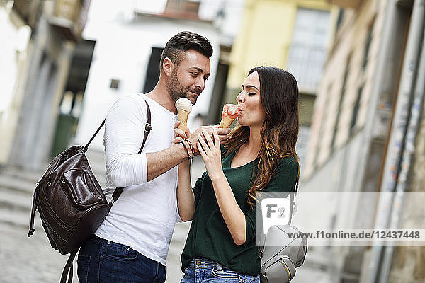 Tourist couple sharing ice cream cones in the city