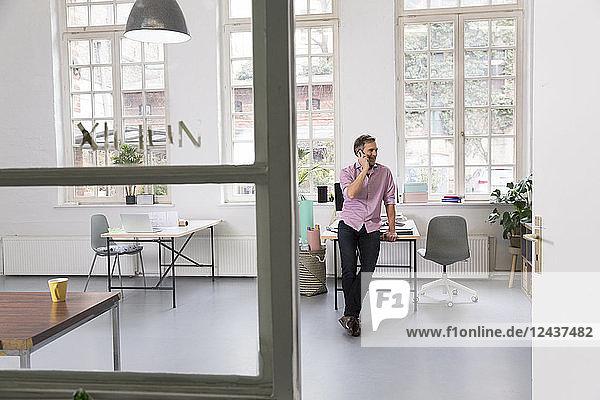 Man talking on cell phone in a loft office