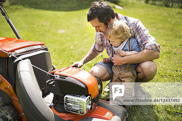 Father with his little son and lawn mower