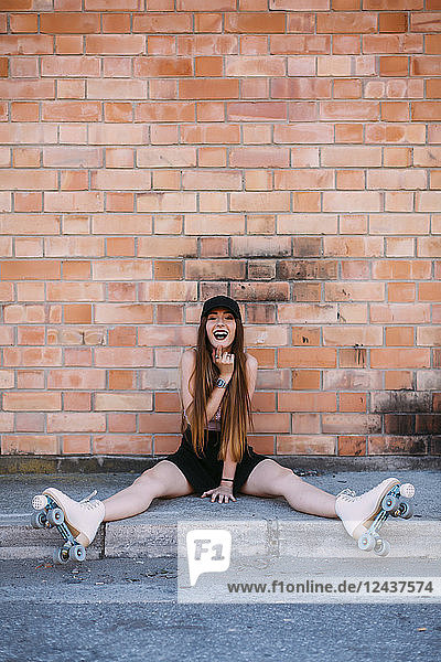 Portrait of laughing young woman with roller skates sitting on sidewalk