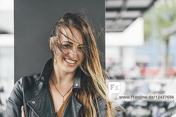 Portrait of happy young woman with windswept hair