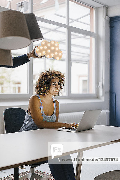 Woman working late in office  hand holding cloud over her head
