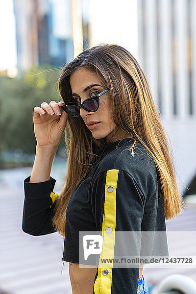 Portrait of attractive young woman wearing sunglasses in the city