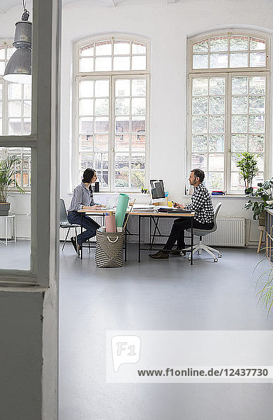 Colleagues working at desk in a loft office