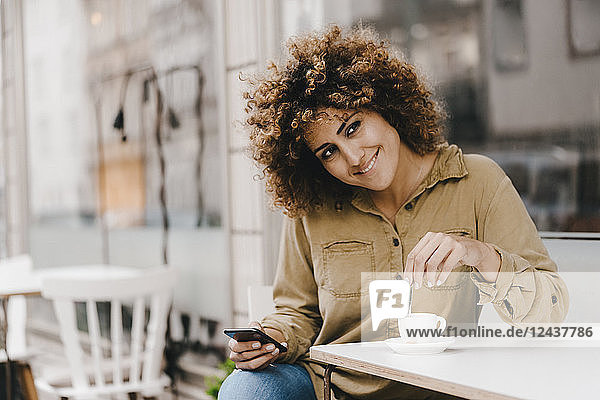 Woman in front of coffee shop  drinking coffee  holding smart phone