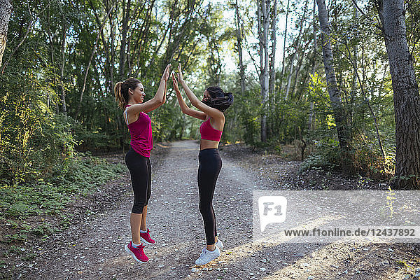 Two active women high fiving in forest