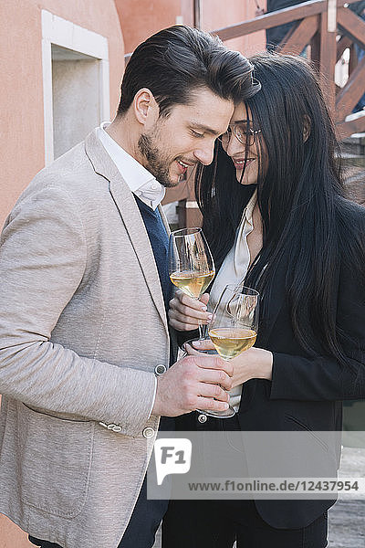 Elegant affectionate couple drinking wine in the city