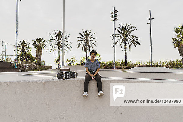Young Chinese man sitting on wall of a skate park near the beach