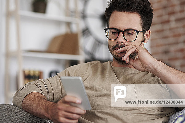 Portrait of man sitting on couch at home looking at smartphone