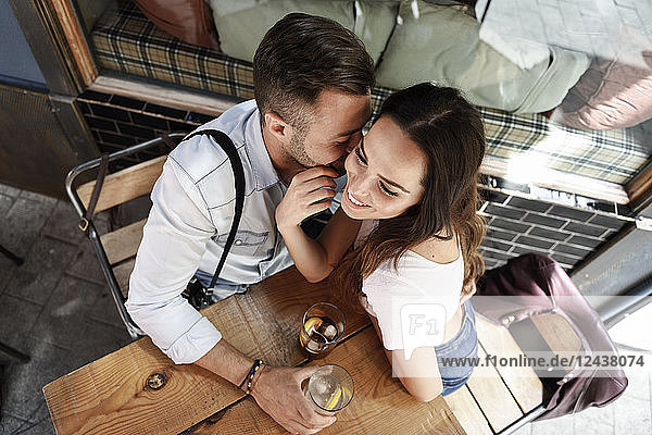 Affectionate couple having a drink at an outdoor bar in the city