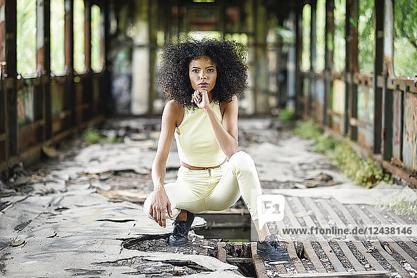 Portrait of fashionable young woman crouching in abandoned and destroyed old train