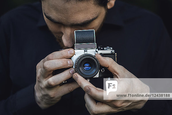 Young man photographing with analogue camera