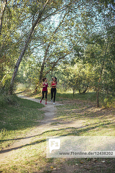Two active women running in forest